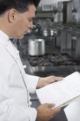 Male chef reading recipe book in kitchen