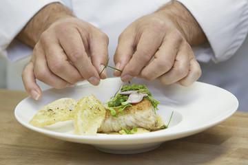 Male chef garnishing food, close-up