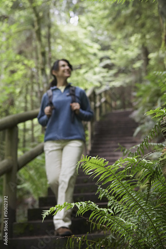 Middle aged woman on forest trail, focus on fern in foreground