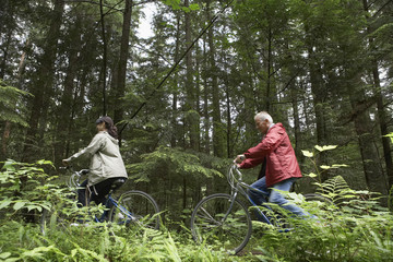Man and woman riding on bicycles in forest, side view