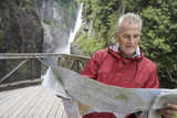 Senior man reading map, waterfall in background