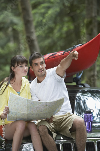 Couple sitting on car looking at map, man pointing