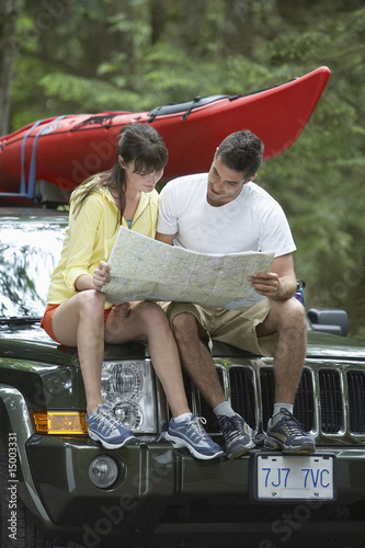 Couple observing map sitting on car