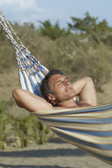 Mid adult man relaxing in hammock