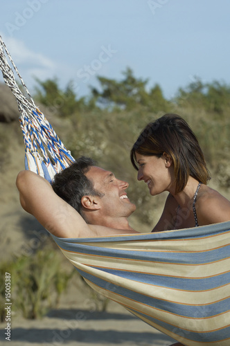 Couple in hammock, laughing, profile