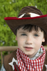 Boy 7-9 wearing cowboy costume, portrait, close-up