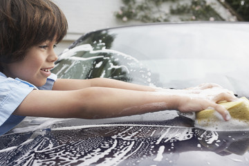 Young boy 7-9 washing car with sponge, side view