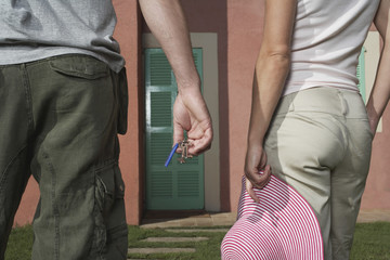 Man and woman in front of house, man holding keys, woman hat