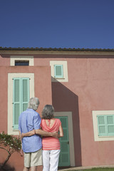 Senior couple in front of house, back view