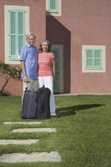 Portrait of senior couple with luggage in front of house