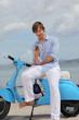 junger mann sitzt auf motoroller und liest sms