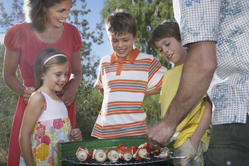 Family with three children 6-11 grilling in garden