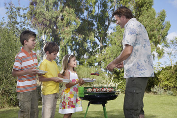 Father serving grilled food to children 5-11 in line