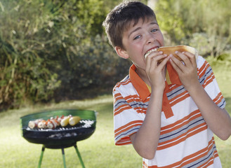 Portrait of boy 10-12 eating frankfurter, barbecue grill in background