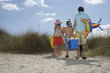 Parents and three children 6-11 carrying beach accessories, back view