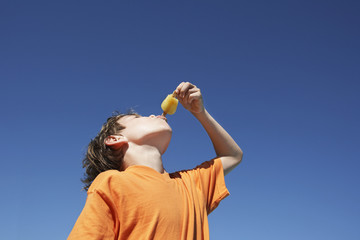Boy 7-9 eating popsicle, blue sky