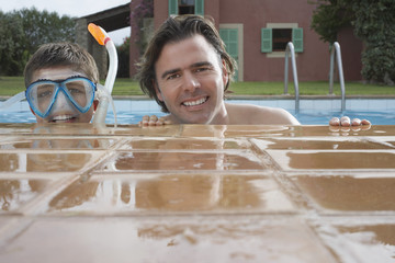 Portrait of father and son 10-12 in pool, boy in snorkelling mask, smiling