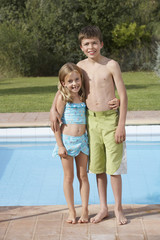 Portrait of sister and brother 6-11 by pool, smiling