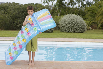 Boy 10-12 blowing up air mattress by pool