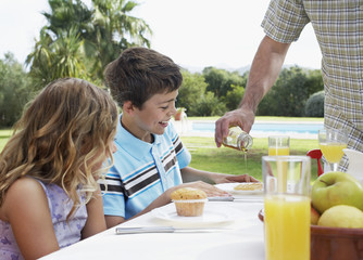 Two children at table 6-11 father pouring syrup