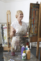 Mature female artist painting at easel in art studiocanvas in studio