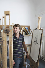 Young male artist standing by charcoal portrait in studio