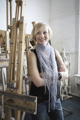 Female student standing among easels in art college