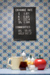 Trading board on wall with wallpaper, containers and mug, selective focus