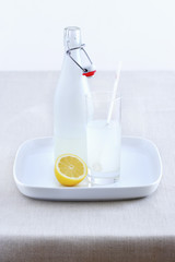 Ceramic bottle, lemonade glass and lemon on tray