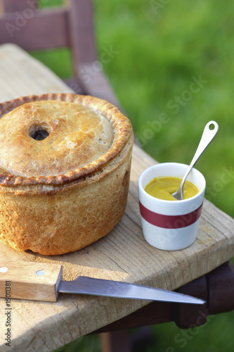 Pork pie, knife and cup of mustard on table outdoors