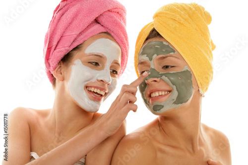 Leinwanddruck Bild Two teenage girl applying facial cream