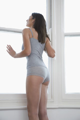 Young woman in underwear, looking out of bedroom window