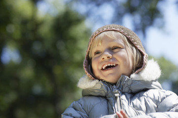 Portrait of young girl 3-4 in winter clothes, laughing