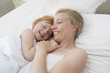 Mother embracing daughter 5-6 in bed, smiling