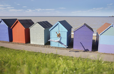 Woman jumping in front of beach hut