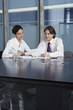 Business man and woman working at table in conference room