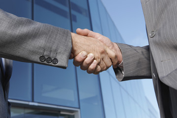 Two business men shaking hands outside office, close-up