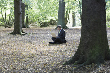 Mid adult business man sitting cross-legged in middle of forest, working on laptop