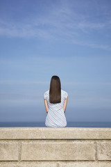 Young woman sitting on stone ledge, back view