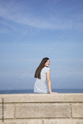 Young woman sitting on stone ledge, back view, portrait