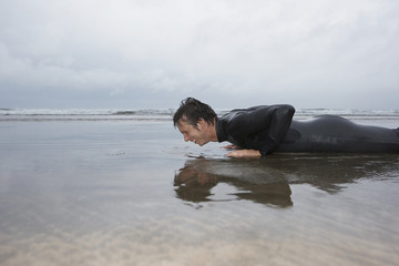 Man in wetsuit doing pushups in shallow water on beach, side view