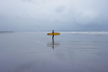 Lone surfer standing in shallow water, side view