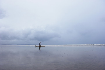 Lone surfer sitting on surfboard in shallow water, side view