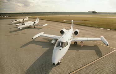Three jet plains at airport, helicopter in background, elevated view