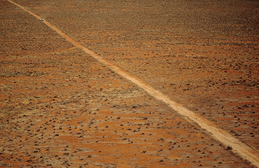 Car driving along desert road, outback Australia