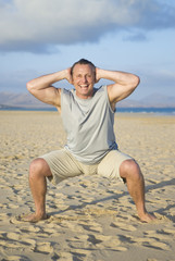 man performing exercises on beach.