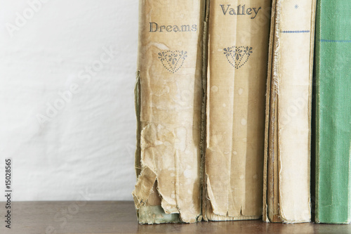 Stack of old books on wooden chest, close up