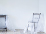 Chair and table covered by plastic in empty room