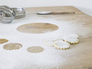 Pastry cutters, cookies and flour scattered on table, close up
