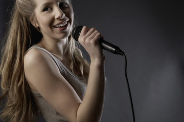 Young woman singing in studio, close-up
